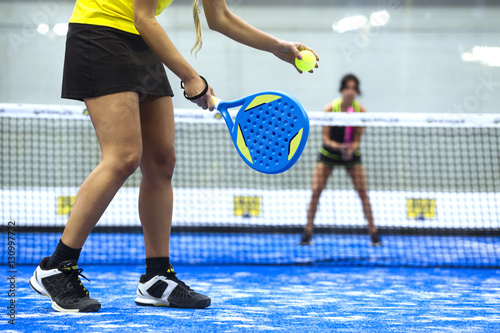 Two young women playing paddle tennis. Poster