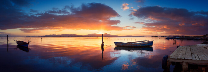 Colorful sunset at the pond with specular reflection with moored fisherman boat © Stefano Garau