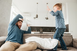 Happy young father fighting by pillows with his little son.