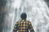 Fototapety Man enjoying waterfall Travel Lifestyle adventure concept vacations into the wild wearing cozy shirt and hat