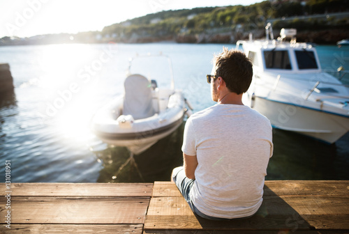 Man enjoying time at seaside, sitting on wooden pier. Plakat