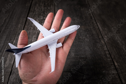 Poster White blank toy of passenger plane on male palm hand over rustic