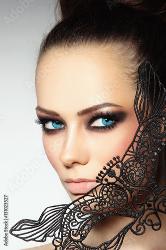 Close-up portrait of young beautiful woman with smoky eyes and lacy black mask Poster