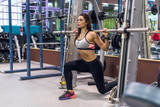 Fit girl doing lunges with the smith machine