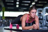 Fototapety Shot of a fit young woman doing stretching workout on the gym floor.