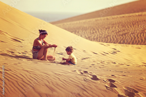 Tuinposter Canarische Eilanden Mother with son playing with sand in a desert in Gran Canaria