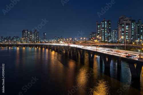 Lit residential district along the Han River and traffic on a bridge in Seoul, South Korea, at night Poster