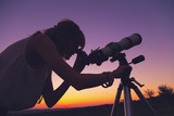 Girl looking at the stars through a telescope.
