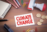 Climate Change. Wooden office desk with stationery, money and a note pad.