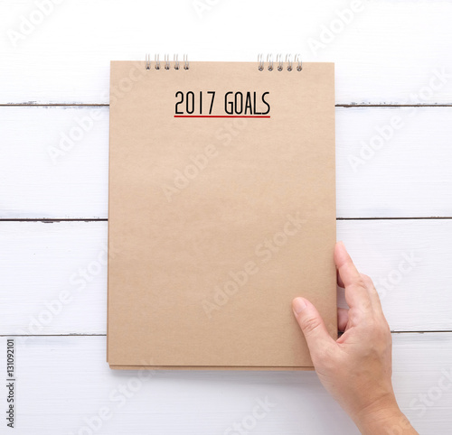 Hand holding recycle paper notebook with 2017 goals Poster