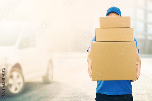 delivery man holding pile of cardboard boxes in front. copy spac