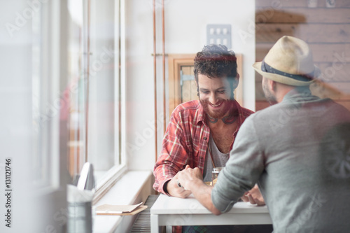 Poster Gay couple sat holding hands in cafe