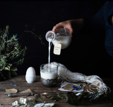 rustic still life. female hand is pouring milk from a jug into  glass. dark background.