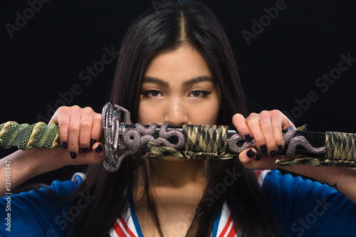 Asian lady holding sword in front of her in studio Poster