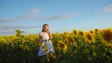 Teenage girl talking on the phone in the colors yellow sunflower girl is holding a phone in his hand on a field of sunflowers on a background of blue sky
