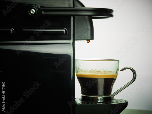Poster Closeup coffee maker pouring hot coffee espresso into glass cup