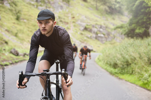 Poster Young road cyclist dressed in black, winning a race with friends
