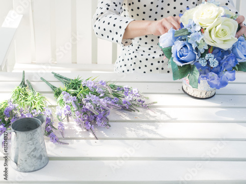 Foto op Canvas Lilac Close-up of young woman in dot pattern dress and hold blue flowers .