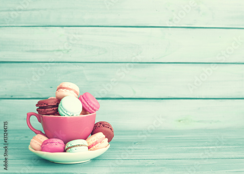 Pastel french macarons in a pink cup over turquoise wood Poster