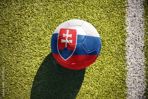 Poster football ball with the national flag of slovakia lies on the field