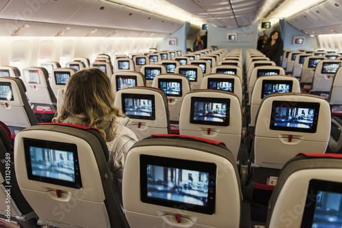 Seats on board of airplane. Cabin of economy class with screens