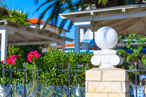 Summer travel vacation in Greece, traditional architecture detail, garden and red roof background