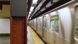 A Manhattan subway train leaves the platform. Blank sign on pillar for customization.   - 131344333