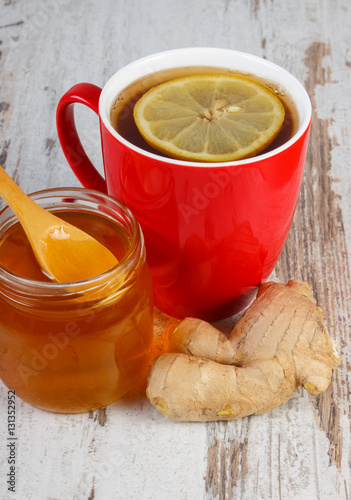 Poster Honey, ginger and cup of tea with lemon on wooden table, healthy nutrition