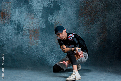 Young man break dancing on wall background. Poster