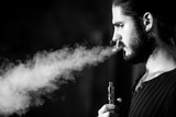 young bearded hipster man smokes electronic cigarette.
