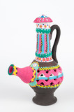 Front view of Nubian style decorated colorful handcrafted pottery jug on white background