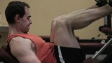Close-up of man in gym training at leg press.