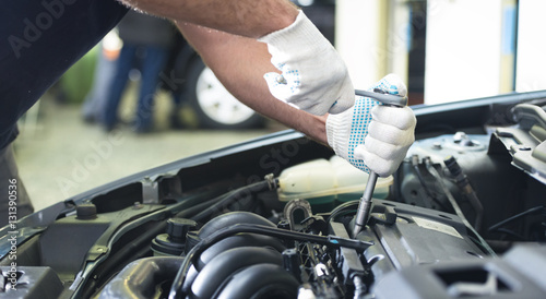 Hands of car mechanic with a wrench, fixing engine in auto repair service.