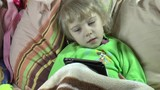 Girl 4 years with soft hair and green pajamas, lying on a bed under a blanket, with a temperature in the disease state, talking with friends on social networks, using a tablet computer