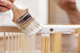 Man painting wood furniture with a brush and paints, close-up - 131421180