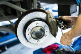 Scene of mechanic assembling Car DiscBrake. selective focused.