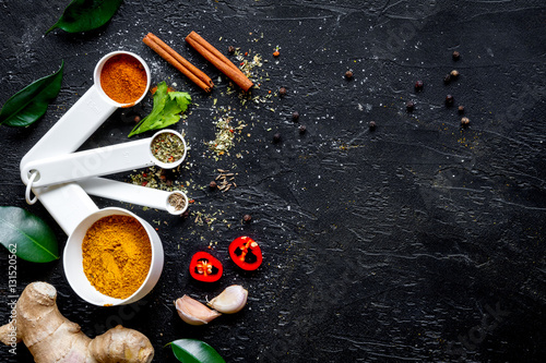 Póster spices in wooden spoons on dark background top view