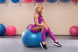 Fitness woman doing exercise with fit ball, athletic girl in sportswear on a pilates ball