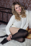 beautiful happy young blond woman with a smile is in the bedroom on the bed with fur in jacket and black leggings