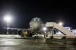 Front view of ground handling passenger airplane at night