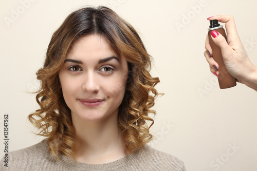 Poster Hairdresser fixing woman hair with hairspray on a light background