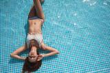 Красивая девушка загорает в бассейне - 131551174