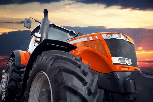 Poster Tractor on a background cloudy sky