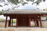 Wooden gate and stone wall next to the Jeongjeon - the main hall of the Jongmyo Shrine in Seoul, South Korea, viewed from the front.