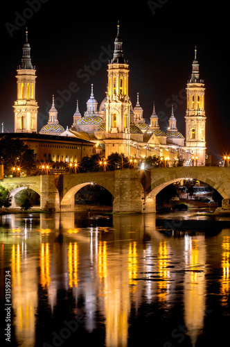 Cathedral-Basilica of Our Lady of the Pillar and the Roman bridge on a summer night in Zaragoza, province Aragon, Spain