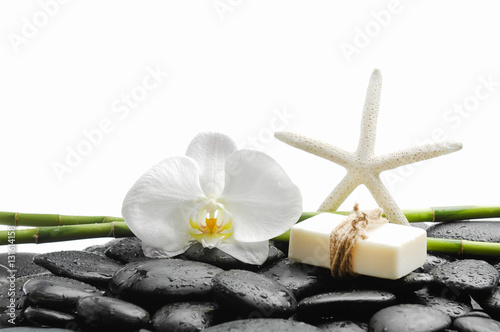Poster Spa White orchid with black stones ,grove,soap with starfish on wet background