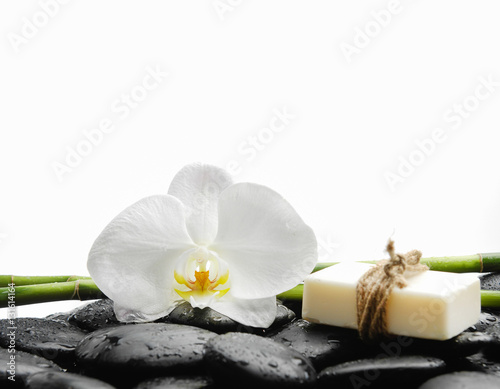 Poster Spa White orchid with black stones ,grove,soap on wet background