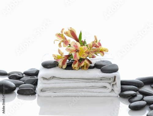 Plexiglas Spa Yellow branch orchid on white towel with pile of stones