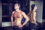 Muscular young man resting in gym during workout