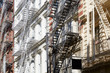 Houses facades with fire escape stairs, sunny day in New York